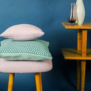 janie knitted textile merino wool two cushions with honeycomb pattern one light pink and blue on a stool