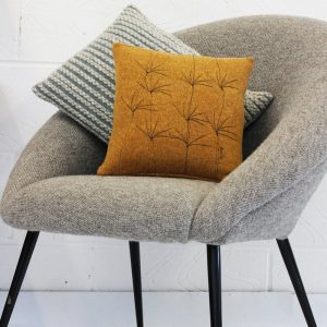 janie knitted textiles two cushion in a grey chair one light brown with tree effect stitching and oblong cushion