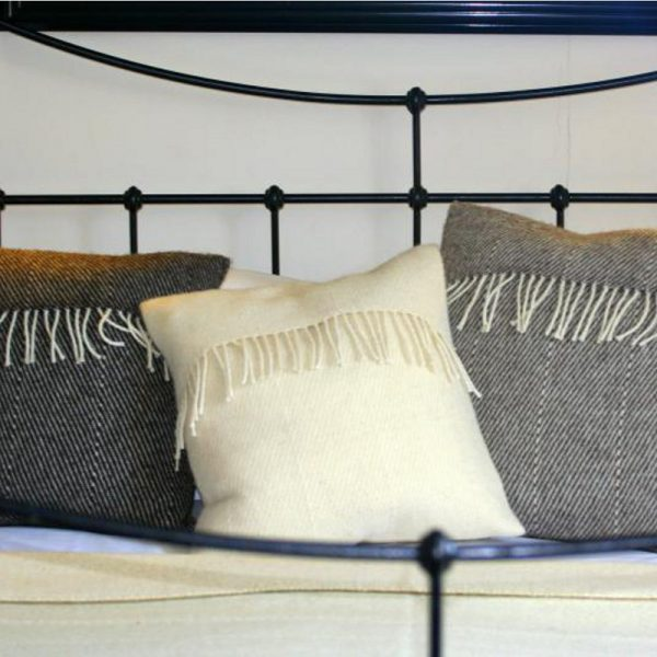 Romney Marsh Wool three cushions blue cream and grey with cream fringe on a wrought iron bed