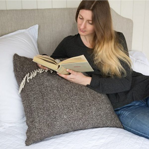 Romney Marsh Wool light brown cushion with cream fringe shown on a bed with a women resting on it reading a book