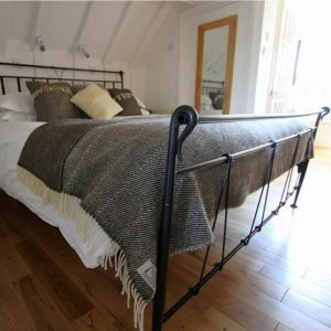 Romney Marsh Wool dark grey throw with cream fringe shown on a wrought iron bed