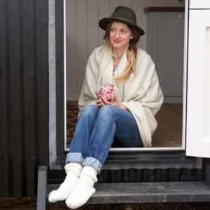 Romney Marsh Wool plain cream throw wrapped around girl wearing a large hat sat on steps