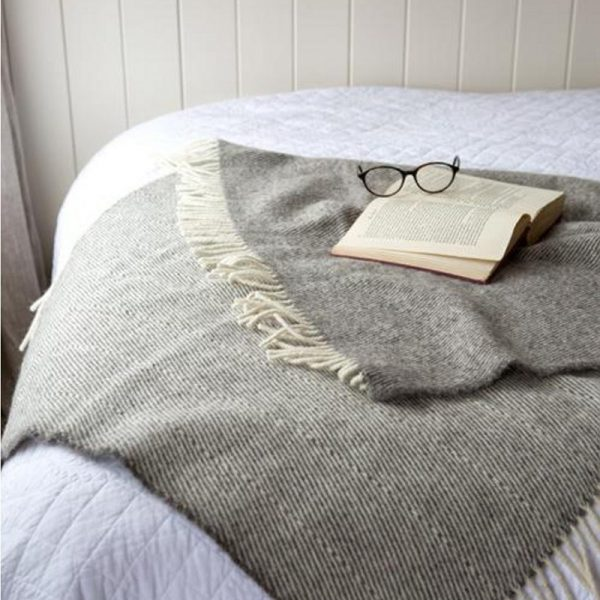 Romney Marsh Wool grey throw with cream fringe on a bed