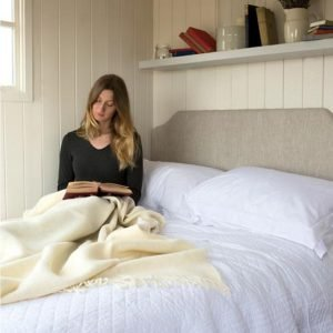 Romney Marsh Wool cream throw women on bed wrapped in throw reading book