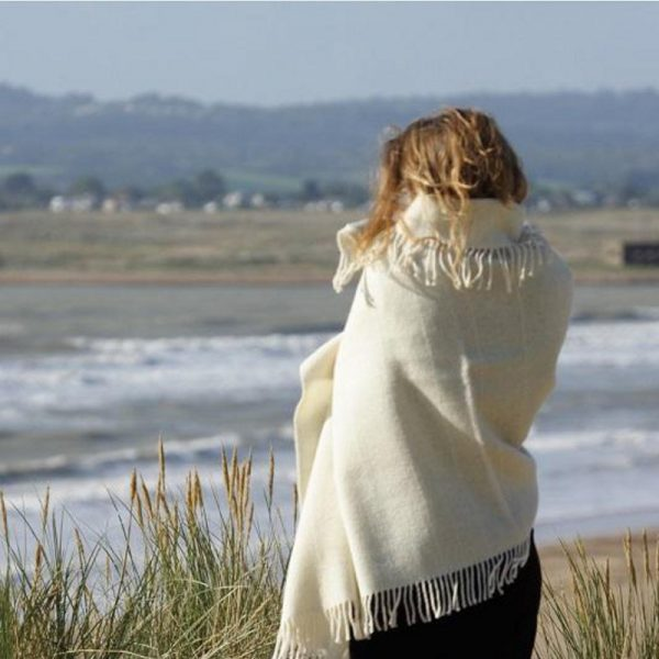 Romney Marsh Wool cream throw wrapped around women looking our to sea