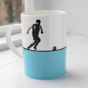 the art room china mug shadow image of a footballer kicking a ball on a light blue and white back ground