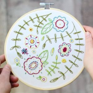 hooped embroidery kit spring flowers embroidered on it in pinks greens yellow