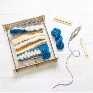 small weaving loom with blue, white and yellow wool