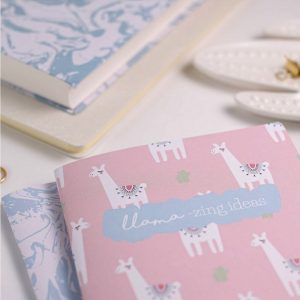 pink notebook with white llama illustrated on it