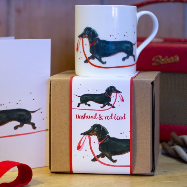 China Mug illustrated with a black dashund holding a red lead