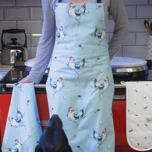 Cotton Apron light blue with chickens and feathers and eggs illustrated on it