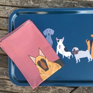 Melamine dark blue tray with a salmon pink tea towel resting on top all with images of dogs