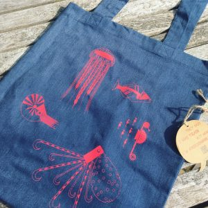 A blue eco friendly tote bag with red illustrations of sealife creatures