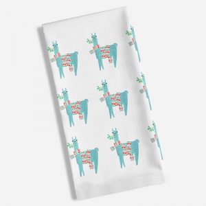 A white tea towel with a repeat image of alpha holding mistletoe in it's mouth and a long Christmas scarf around it's middle