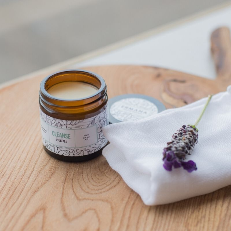 A pot of cleanse balm on a table with a sprig of lavender