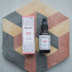 a bottle of renew face oil natural skin care with neroli and ylang ylang on a tile
