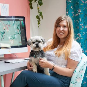 Portrait image of Lorna Syson sitting in her office with her dog