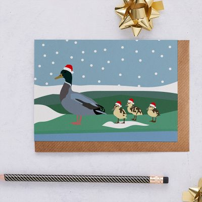 Blank Greeting card with an illustration of a mother duck and three ducklings all wearing Christmas hats sitting in the snow