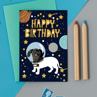 Happy Birthday greeting card with a navy background and an illustration of a dog in space