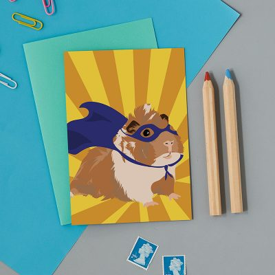 Greeting card with a super hero guinea pig wearing a blue cape and mask