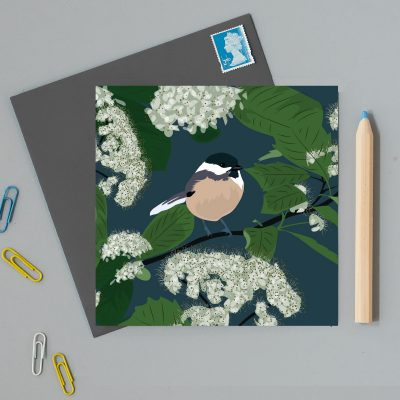 navy blue greeting card with illustration of a bird sitting on on a branch surrounded by flowers