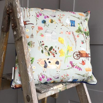 Cushion on a ladder decorated in country inspired duck, pig, wellies, flowers