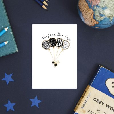 Birthday greeting card with an image of a bee being lifted in the air by balloons