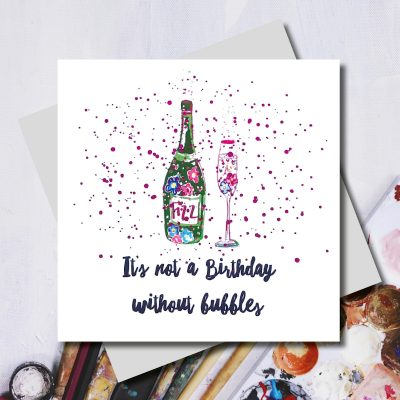 birthday card with a bottle of fizzy wine and a glass and pink fizz as a background