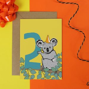 a yellow birthday card featuring a koala with a party hat on it's head holding a large number 2