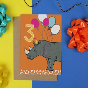 an orange birthday card featuring a rhino with balloons around it's neck and a large number 3