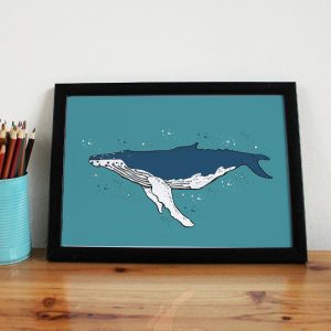 a framed print of a humpback whale on a blue background