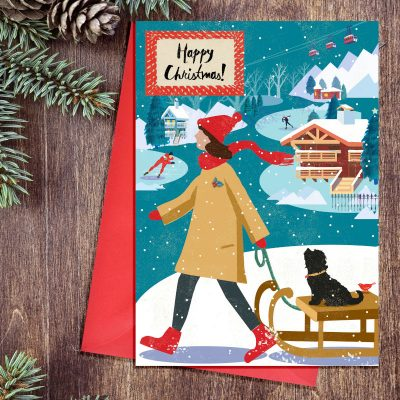 Christmas card in a retro Nordic style featuring a lady pulling a dog along on a sledge in the snow