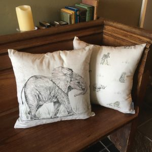 100% unbleached cotton cushion printed with an elephant and other endangered animals displayed on a bench
