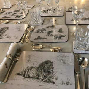 a table display set up with placemats, coasters and chopping boards from the endangered animal range from Sweet Design